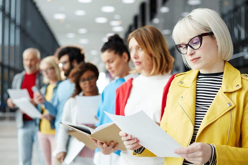 Blond Young Woman In Eyeglasses Reading Her Resume While Standing In Queue And Waiting For Her Turn For Interview